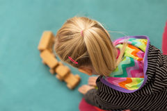 Blond girl is playing with a wooden toy Royalty Free Stock Images