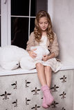 Blond girl with polar bear toy Royalty Free Stock Photos