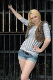 Blond girl posing against metal gate Royalty Free Stock Images