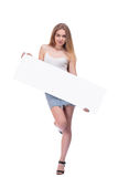 Blond girl posing with big nameplate isolated on white background. Blond young woman posing with big nameplate isolated on white background Royalty Free Stock Image
