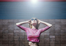 Blond girl posing in pink striped blouse and sun glasses, looking up with head and hands thrown back. Day,outdoor royalty free stock image