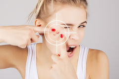 Blond girl pressing out blemishes from her face,with targe Stock Images