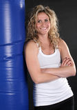 Blond Girl With Punching Bag. Cute young woman resting with a heavy punching bag with a happy expression Royalty Free Stock Photography