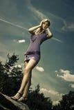Blond girl in purple dress. Outdoor blond girl in purple dress, blue sky Stock Photo