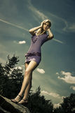 Blond girl in purple dress. Outdoor scene Royalty Free Stock Photos