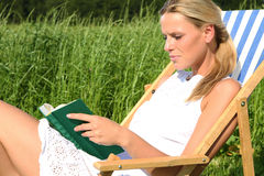 Blond Girl reading a book. Blond Girl sitting in a sun-chair and reading a book royalty free stock photos