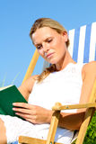 Blond Girl reading a book. Blond Girl sitting in a sun-chair and reading a book royalty free stock images