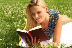 Blond Girl reading a book. Blond Girl laying in the grass and reading a book stock photography
