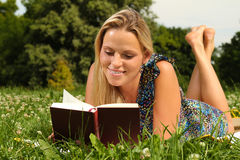Blond Girl reading a book. Blond Girl laying in the grass and reading a book royalty free stock photography