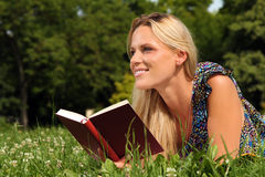 Blond Girl reading a book. Blond Girl laying in the grass and reading a book royalty free stock images