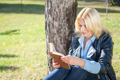Blond girl reading a book in the park Stock Photos