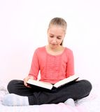 Blond girl reads interesting book sitting on bed Royalty Free Stock Photo