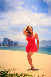 Blond girl in red dances barefoot on sand with hands above. Blond slim girl in short red frock dances barefoot on sand beach hands above against azure sea wind royalty free stock photos