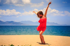 Blond girl in red dances barefoot on sand with hands above. Blond slim girl in short red frock dances barefoot on sand beach hands above against azure sea wind royalty free stock photography