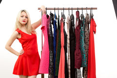Blond girl in a red dress. front of clothes hanger. Stock Images