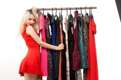 Blond girl in a red dress. front of clothes hanger. Royalty Free Stock Photos