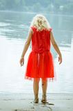 Blond girl in red dress at the river strand Stock Photography