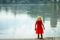 Blond girl in red dress at the river strand Royalty Free Stock Photography