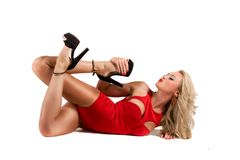 Blond girl in red dress and shoes lying on floor Royalty Free Stock Photography