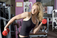 Blond girl with red dumbbell Royalty Free Stock Image