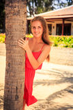 Blond girl in red leans out of palm looks into camera. Blond slim girl in short red frock leans out of palm trunk looks into camera against tropical plants and royalty free stock images