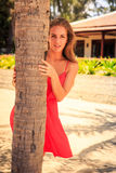 Blond girl in red leans out of palm looks into camera. Blond slim girl in short red frock leans out of palm trunk looks into camera against tropical plants and royalty free stock photography