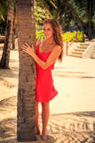 Blond girl in red leans out of palm looks into camera. Blond slim girl in short red frock leans out of palm trunk looks into camera against tropical plants and stock photography