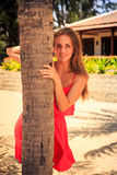 Blond girl in red leans out of palm. Blond slim girl in short red frock leans out of palm trunk stand against tropical plants and villa royalty free stock photography