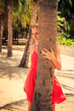Blond girl in red looks out of palm looks forward against plants. Blond slim girl in short red frock looks out of palm trunk and looks into distance against royalty free stock image