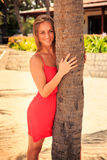 Blond girl in red looks out of palm looks forward against plants. Blond slim girl in short red frock looks out of palm trunk and looks into distance against royalty free stock images