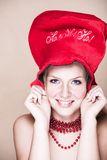 Blond girl in red necklace and hat royalty free stock photography