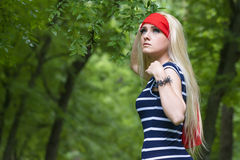 Blond girl with red scarf and striped dress in the forest Stock Image