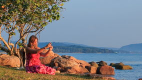 Blond Girl in Red Sits on Beach Takes Photo at Sunset by Rocks. Blond girl in red frock sits on grass beach under tree near rocks takes photos of sea and hills stock video