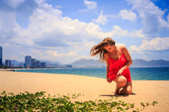 Blond girl in red squats on sand wind shakes long hair. Blond slim girl in short red frock squats on sand beach looks downwards against azure sea and city wind stock image