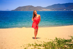 Blond girl in red stands barefoot on sand beach at noon. Blond slim girl in short red frock stands barefoot on sand beach against azure sea and hills at noon stock photo