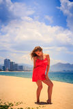 Blond girl in red stands on beach smooths shaken by wind hair. Blond slim girl in short red frock stands on sand beach smooths shaken by wind long hair against stock images