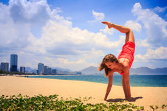 Blond girl in red stands in gymnastic position hands leg scale. Blond slim girl in short red frock stands in gymnastic position hands leg scale on sand beach stock photography