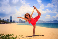 Blond girl in red stands in gymnastic position leg scale on sand. Blond slim girl in short red frock stands in gymnastic position leg scale on sand beach against stock photo