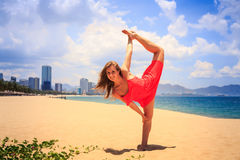 Blond girl in red stands in gymnastic position leg scale on sand Stock Photography