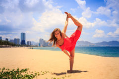 Blond girl in red stands in gymnastic position leg scale on sand. Blond slim girl in short red frock stands in gymnastic position leg scale on sand beach against royalty free stock images