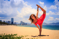 Blond girl in red stands in gymnastic position leg scale on sand. Blond slim girl in short red frock stands in gymnastic position leg scale on sand beach against royalty free stock photos