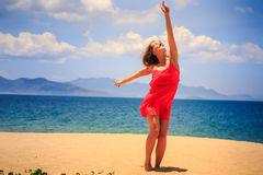 Blond girl in red stands on sand beach lifts hand points to sun Stock Photos