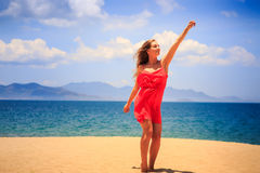 Blond girl in red stands on sand beach lifts hand up. Blond slim girl in short red frock stands on sand beach lifts hand up against azure sea wind shakes long royalty free stock images