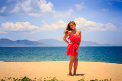 Blond girl in red stands on sand holds hand on hip at noon Stock Images