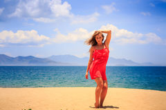 Blond girl in red stands on sand holds hand on hip at noon. Blond slim girl in short red frock stands barefoot on sand beach holds hand on hip against azure sea royalty free stock photos