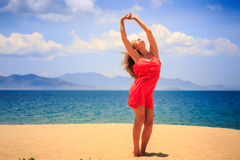 Blond girl in red stands on sand lifts hands over head. Blond slim girl in short red frock stands on sand beach lifts hands over head against azure sea wind royalty free stock images