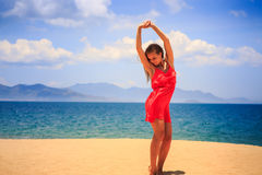 Blond girl in red stands on sand lifts hands over head Stock Image