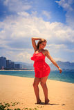 blond girl in red stands on sand puts hands on head back Royalty Free Stock Photography