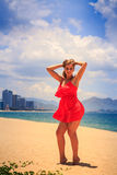 blond girl in red stands on sand puts hands on head back Royalty Free Stock Photo
