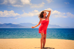 Blond girl in red stands on sand touches head and looks upwards Royalty Free Stock Image